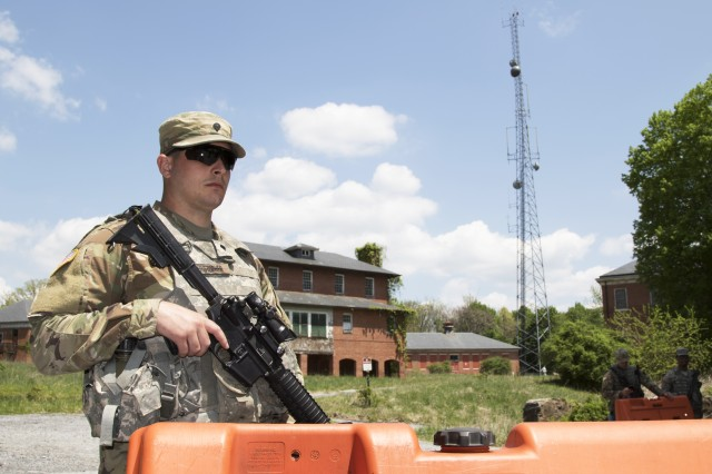 Spc. Ryan Christopher from D Company, 175th Infantry Regiment, Maryland National Guard, stands guard at a tactical control point as part of Vigilant Guard 18 on May 8, 2018 in Sykesville, Maryland. The defensive perimeter was designed to secure a hypothetically-downed cell tower, background.