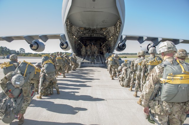 Heavily-laden paratroopers board a U.S. Air Force C-17 aircraft prior to conducting static line operational testing of the Modular Lightweight Load-Carrying Equipment (MOLLE) 4000 Airborne Rucksack.