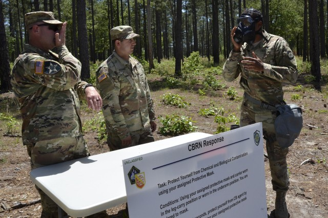 Army Cyber Protection Brigade Soldiers acting as trainers and evaluators demonstrate putting on a chemical protective mask during warrior skills training at the CPB Cyber Stakes exercise at Fort Gordon, Ga., May 3, 2018. Cyber Stakes, the brigade's flagship biannual training event, provides CPB Soldiers and civilian employees with three days of instruction, collaboration and evaluation of core cyber skills, followed by two days of training and testing on basic Army warrior tasks for brigade troops.