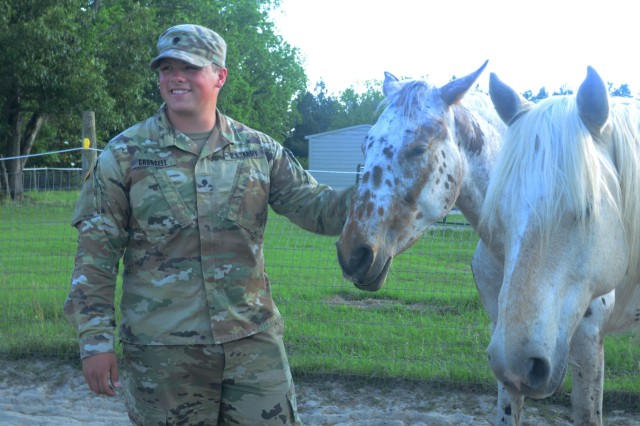 Spc. Chris Cronsell, 3rd Combined Arms Battalion, 15th Infantry Regiment, 2nd Armored Brigade Combat Team, 3rd Infantry Division, tends to horses in the field May 7, 2018, at Second Chances Equine Rescue, Inc., in Hinesville, Ga. The mission of the organization is to assist and educate horse owners, rehome, rescue, rehabilitate and adopt or offer sanctuary to horses in need. (U.S. Army photo by Spc. Noelle E. Wiehe, 50th Public Affairs Detachment, 3rd Infantry Division/ Released)