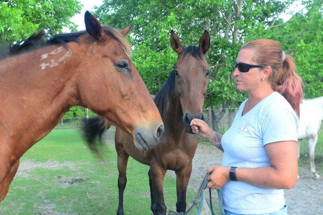 Andrea Doolittle, founder and president of Second Chances Equine Rescue, Inc., in Hinesville, Ga., speaks to a few horses in the field before feeding time May 7, 2018. Doolittle, a U.S. Air Force veteran, founded the rescue in August 2013 when she saved two horses - Spirit and Cinnamon - from being sent to a slaughterhouse. (U.S. Army photo by Spc. Noelle E. Wiehe, 50th Public Affairs Detachment, 3rd Infantry Division/ Released)