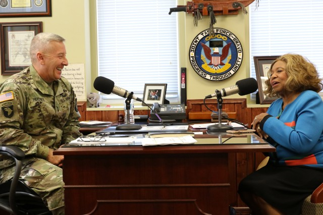 "Maj. Gen. Chris Hughes shares a laugh with Regina Prude, from the SiriusXM radio program, ""The Leadership Zone,"" during an interview in his office Oct. 4, 2017. (Photo by Michael Maddox 