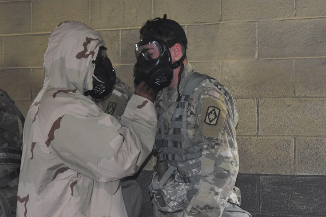 Sgt. Kevin Dickens, a chemical NCO from Headquarters and Headquarters Battery, 75th Field Artillery Brigade, helps Pfc. Ronald Griswold correctly don his protective mask, April 30, 2018, at Fort Sill, Okla.