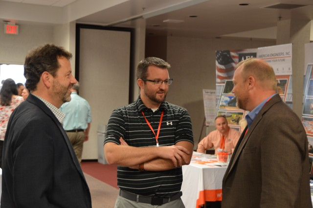 Two representatives from small firms discuss contracting opportunities with Huntington District's Brandon Lewis.