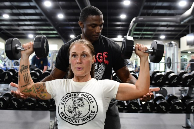 Lacey Hancock works out with dumbbells in Smith Physical Fitness Center while Curtis Nelson spots her. The two have become close friends as they share their love of bodybuilding and fitness with others. (Photo by Eric Pilgrim | The Gold Standard)