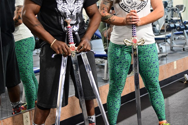 Curtis Nelson and Lacey Hancock show off their sword trophies from the recent Derby bodybuilding competition. (Photo by Eric Pilgrim | The Gold Standard)
