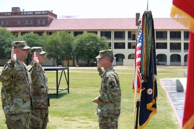 (FORT BENNING, Ga) - Brig. Gen. Neil S. Hersey, Commandant, U. S. Army Cyber School, Fort Gordon administers the oath of office to 1st Lt. James J. Gusman (far left) and 1st Lt Timothy J. Hennessy during the Cyber Direct Commissioning Ceremony on Taylor Field at Fort Benning, May 9.