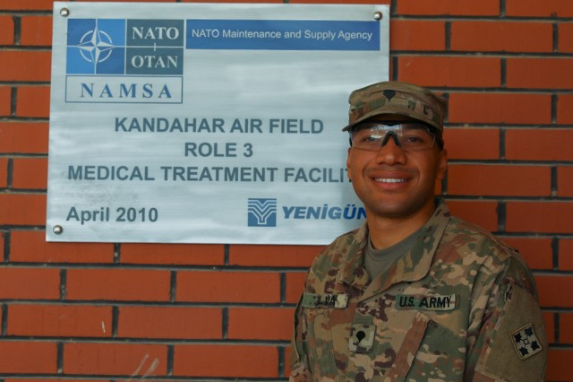 Spc. Daimon Silva, a medical logistics specialist assigned to Charlie Company, 704th Brigade Support Battalion, 2nd Infantry Brigade Combat Team, 4th Infantry Division, poses in front of the NATO Role III Multinational Medical Unit sign, April 20, 2018, in Kandahar Airfield, Afghanistan. (U.S. Army photo by Staff Sgt. Neysa Canfield/TAAC-South Public Affairs)