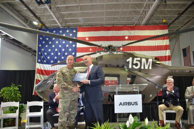 Col. Billy Jackson, PEO Aviation's Utility Helicopters Project Manager receives the aircraft log book from Scott Tumpak, Airbus Helicopters Vice President of Government Programs marking the acceptance of the latest UH-72A Lakota light utility helicopter into the Army inventory.  The aircraft was handed over to the Army during a ceremony May 4 at the Airbus Helicopters production facility in Columbus, Miss.