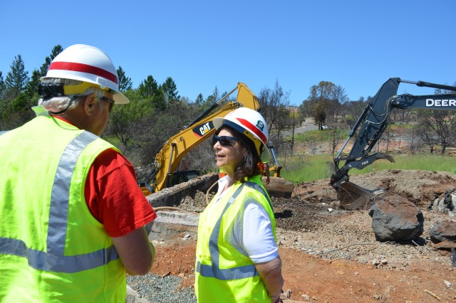 Cheryl Michener (right), discusses debris removal operations at a fire-damaged home site in Sonoma County, California, with John Jones. Both Michener and Jones are rehired annuitants who voluntarily deployed with the U.S. Army Corps of Engineers to Northern California in support of disaster relief operations.