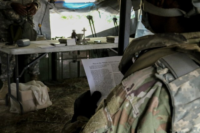 Fort Polk, La., May 13, 2018 - A Georgia Army National Guardsman reads the handouts during the 177th Brigade Support Battalion religious services at the Joint Readiness Training Center Rotation 18-07.  Religious services are held consistently during the rotation by National Guard chaplains to maintain the spiritual welfare of the Soldiers.