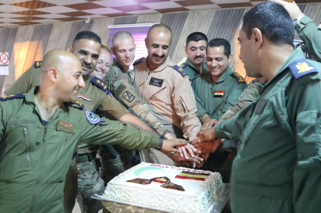 The 449th Combat Aviation Brigade, United Kingdom Training Team 1 (Armored Medical Regiment) and Iraqi army aviation medical staff celebrate the completion of the phase one 10-day aeromedical evacuation training course facilitated by the 449th CAB by collectively cutting cake at Camp Taji, Iraq, May 3, 2018.