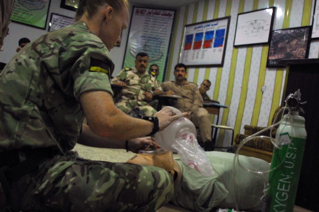 Staff Sgt. Natalie Jackson, assigned to the U.K. Training Team 1, Armored Medical Regiment, demonstrates how to bag valve mask on a medical dummy during a 10-day aeromedical evacuation training course facilitated by the 449th Combat Aviation Brigade, which requires Iraqi students to simulate providing point-of injury care and medical evacuations to a multi-trauma patient at Camp Taji, Iraq April 22-May 3, 2018.