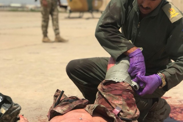 An Iraqi medical scientist assigned to the Iraqi army aviation simulates applying combat gauze to a multi-trauma patient suffering from a double amputation during the 449th Combat Aviation Brigade's aeromedical evacuation training course at Camp Taji, Iraq April 22 - May 3, 2018.