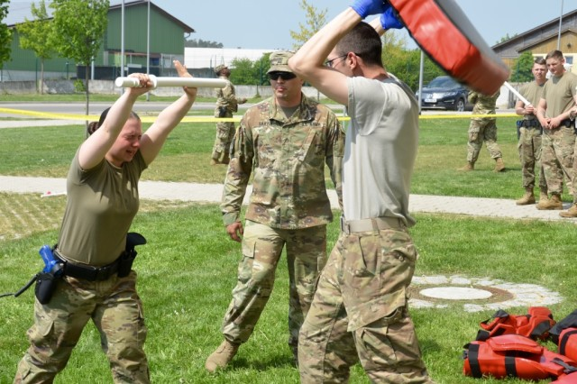 "Pvt. Second Class Rose Hollywood fights off an ""assailant"" while dealing with the effects of pepper spray during a recent OC training as part of Installation Law Enforcement Certification at USAG Ansbach May 4, 2018. Her trainer, Staff Sgt. Scott Martin, Interservice Non-lethal Individual Weapons Instructor, observes her actions closely."