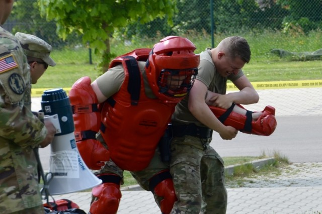 Pvt. Second Class Michael Edwards wrestles a 'suspect' to the ground while dealing with the effects of pepper spray during a recent OC training as part of Installation Law Enforcement Certification at USAG Ansbach May 4, 2018.