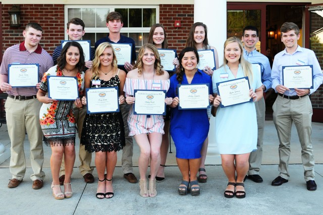 Awardees pose with their scholarships after the Fort Rucker Community Spouses Club Scholarship Award Ceremony at the Allen Heights Community Center May 7.
