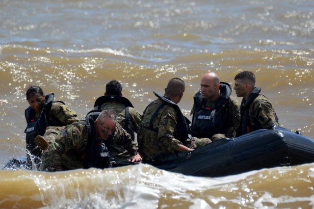 """Soldiers assigned to 3rd Brigade Combat Team, """"Broncos,"""" 25th Infantry Division, disembark from their F470 Zodiac [combat rubber raiding craft] during a Mungadai exercise off the coast of Marine Corps Training Area Bellows Schofield Barracks, Hawaii, on April 18, 2018. The Mungadai is used as a Bronco Brigade leader development program is to create disciplined, trained, and ready professionals, prepared with operational and foundational knowledge, to take disciplined initiative while implementing and executing their commander's intent.  (U.S. Army photo by Staff Sgt. Armando R. Limon, 3rd Brigade Combat Team, 25th Infantry Division)"""