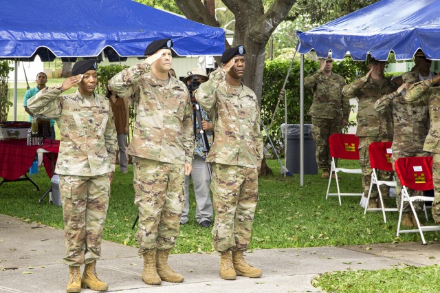 (Pictured from left to right) Outgoing Command Sgt. Maj. Yolanda S. Tate, Pacific Ocean Division Commander Brig. Gen. Thomas J. Tickner, and incoming Command Sgt. Maj. Patrickson Toussaint, salute the colors during the Change of Responsibility Ceremony at Fort Shafter, May 4.