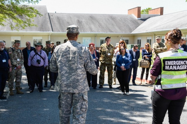 Maj. Stephen Rice, a public affairs officer assigned to the Maryland Defense Force, goes over a schedule of events with distinguished visitors May 9, 2018, at Perry Point Veterans Affairs Medical Center, Perry Point, Md. during Maryland's Exercise Vigilant Guard 18. International partners are present observing the exercise to take home lessons learned.