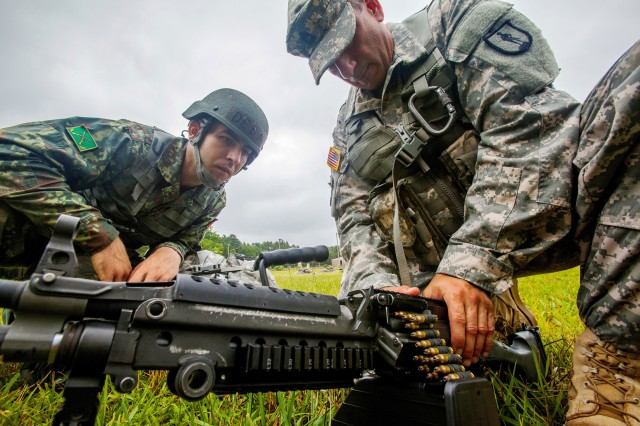 Sgt. 1st Class Harry R. Martinez, right, with the New Jersey Army National Guard, demonstrates how to load an ammunition drum on a M249 squad automatic weapon to Albanian Officer Candidate Endri Deda while training at Joint Base McGuire-Dix-Lakehurst, N.J. The New Jersey National Guard and Albania are paired together as part of the National Guard Bureau's State Partnership Program, which links National Guard elements with partner nations worldwide.