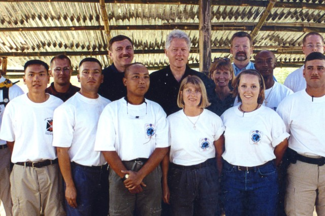 Johnie Webb, left center, deputy of outreach and communications for the Defense POW/MIA Accounting Agency, stands next to then-President Bill Clinton during his visit to an excavation site in this undated photo. Webb, a retired lieutenant colonel and Vietnam War veteran, has worked for the agency for 40 years to help families reunite with their lost loved ones.