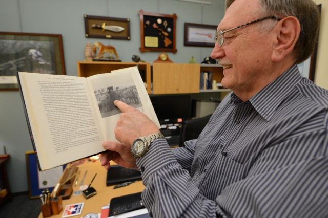 Johnie Webb, deputy of outreach and communications for the Defense POW/MIA Accounting Agency, points to a photo of him published in a book on U.S.-Vietnam diplomatic relations after the war inside his office at Joint Base Pearl Harbor-Hickam, Hawaii, March 13, 2018. Webb, a retired lieutenant colonel and Vietnam War veteran, was part of the first recovery team to enter Vietnam following the war in search of missing American service members.