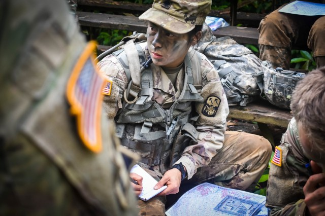 Spc. Emily Moller a chemical, biological, radiological, and nuclear specialist, assigned to the 1st Battalion 1st Air Defense Regiment, 94th Army Air and Missile Defense Command take notes during a the command's 2018 Noncommissioned Officer and Soldier of the year Competition day land navigation lane. The competition took place at multiple training sites in Schofield Barracks, Hawaii the week of 6-11 May 2018.