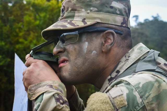 Staff Sgt. Jaime Linares, a satellite communication systems operator-maintainer and assigned to the Headquarters and Headquarters Battery, 94th Army Air and Missile Defense Command shoot a azimuth using the compass-to-cheek technique during the command's 2018 Noncommissioned Officer and Soldier of the Year Competition day land navigation lane. The competition took place at multiple training sites in Schofield Barracks, Hawaii the week of 6-11 May 2018.
