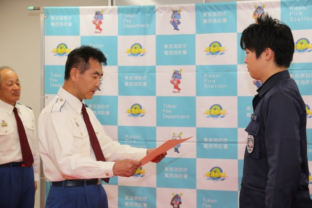 Hiromitsu Moro, left, assistant chief for Tokyo Fire Department, reads the Distinguished Service Award during a recognition ceremony at TFD for Kan Saito, right, guard supervisor, Provost Marshal Office at Hardy Barracks, right, honoring his lifesaving actions that helped save a young boy's life. (U.S. Army photo by Lance D. Davis)