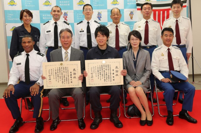 Masayuki Saito, left center, his son Kan Saito, center, guard supervisor, Provost Marshal Office at Hardy Barracks, and his wife Sachiko Saito, right center, seated with members of U.S. Army Garrison Japan's Directorate of Emergency Services and Tokyo Fire Department after being recognized May 9, 2018 by TFD for their actions that helped save a young boy's life. (U.S. Army photo by Lance D. Davis)