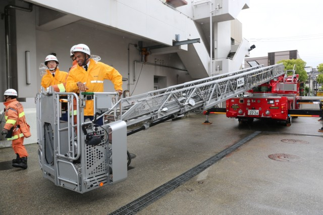 Soldiers from the Directorate of Emergency Services get lifted on the firetruck ladder during a tour held at Tokyo Fire Department May 9, 2018. (U.S. Army photo by Lance D. Davis)