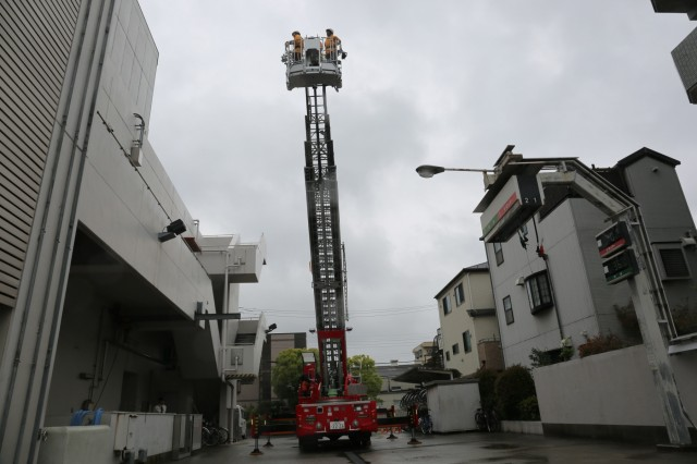 Soldiers from the Directorate of Emergency Services get lifted up to 100 feet on the firetruck ladder during a tour held at Tokyo Fire Department May 9, 2018. (U.S. Army photo by Lance D. Davis)