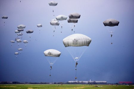 Paratroopers assigned to the 173rd Airborne Brigade, Italian Army Paratroopers and Poland Paratroopers, descend onto Juliet Drop Zone in Pordenone, Italy, during an airborne operation from a U.S. Air Force C-130 Hercules aircraft, April 10, 2018. The 173rd Airborne Brigade is the U.S. Army Contingency Response Force in Europe, capable of projecting ready forces anywhere in the U.S. European, Africa or Central Commands' areas of responsibility.