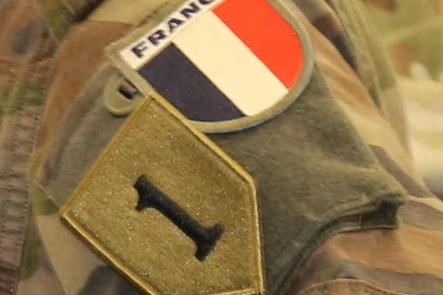 A French Liaison Officer working inside the U.S. Army 1st Infantry Division Headquarters tactical operations wears both U.S. and France military patches on her shoulder during the Joint Warfighting Assessment (JWA) 18.1 at Grafenwohr, Germany, on May 3, 2018. The dual patches highlight the coalition's commitment to a unified force and the improvement of interoperability between forces in a mission partner environment.