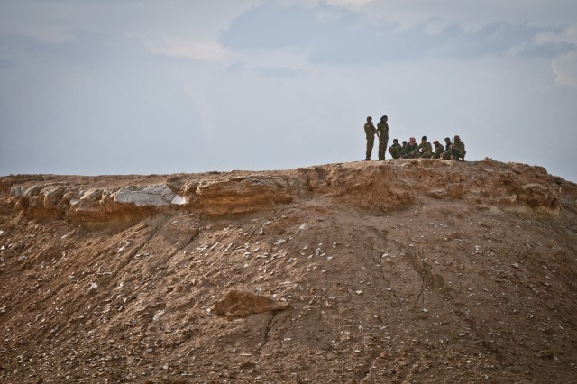Syrian Democratic Forces watch from a local hilltop as Coalition Forces shell known ISIS locations with mortars near the Iraqi-Syrian border as part of Operation Roundup, May 13, 2018. Coalition Forces are working by, with and through their SDF partners as they rid Syria of the final ISIS strongholds. (U.S. Army photo by Staff Sgt. Timothy R. Koster)