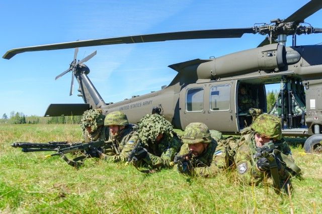 Estonian soldiers of the 2nd Infantry Brigade, Estonian Defence Force, and Finnish combat engineers of the 1st Combat Engineer Company, Pori Brigade, conduct movement to board a Company B, 3rd Assault Helicopter Battalion, 227th Aviation Regiment, 1st Air Cavalry Brigade, 1st Cavalry Division, UH-60 Blackhawk helicopter during a training exercise at an area just outside of Varstu, Estonia, May 9, 2018. The training is part of Operation Hedgehog, a multinational exercise held in Estonia to enhance readiness and interoperability between allies and partners in the Baltic region.