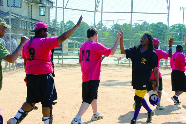 Softball players congratulate each other following a game May 12 at the Hilton Field Sports Complex.