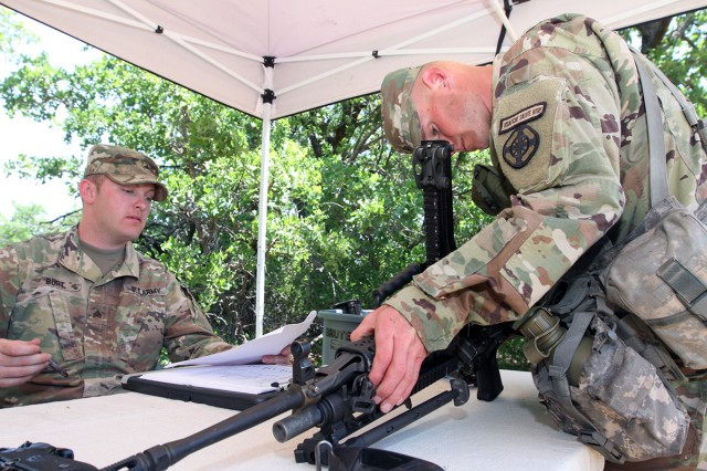 Sgt. Taylor Burt, 2-6th Air Defense Artillery, evaluates a competitor who is reassembling an M249 squad automatic weapon May 10, 2018, at Fort Sill's Camp Eagle.