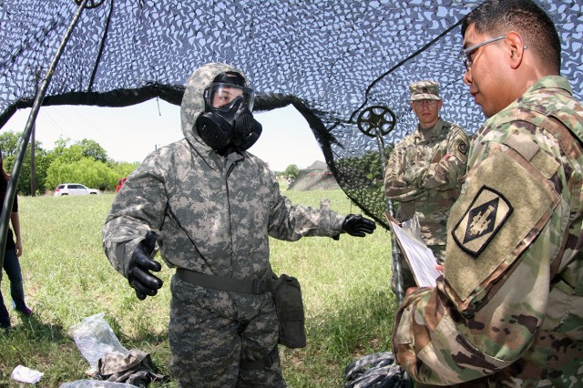 Competitor Sgt. Makayla Highler, 2-18th FA, goes through the Chemical, Biological, Radiological, Nuclear and Explosive, or CBRNE event during the Best Warrior competition May 10, 2018, at Fort Sill. Sgt. Elias Aguirre (far right), 2-4th FA, evaluates her performance. Highler would go on to win the title.