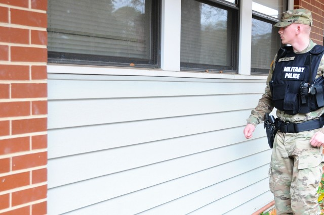 In this file photo, Spc. James Burgess, 6th Military Police Detachment, inspects the windows of a home on Fort Rucker as he performs a quarters check.