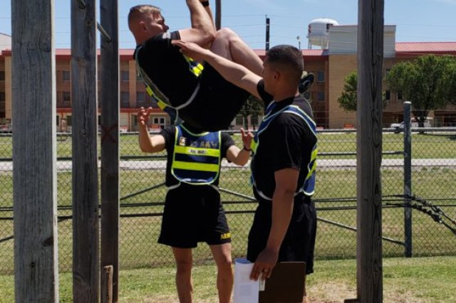 Drill Sergeants (Staff Sgt.) Michael Hnat (rear) and (Sgt. 1st Class) Francisco Soto (front) instruct and provide safety, as Drill Sergeant (Staff Sgt.) Michael Davies demonstrates proper execution of the leg tuck exercise.