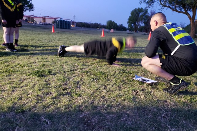 Pfc. James Lambing (center) performs a T-pushup as a fellow drill sergeant grades his technique and other Soldiers observe.