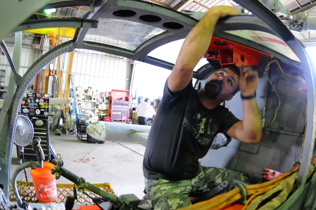 Dennis Grater, chief of maintenance for the restoration, works on the XH-51 Compound helicopter May 15 as part of a restoration project on the aircraft.