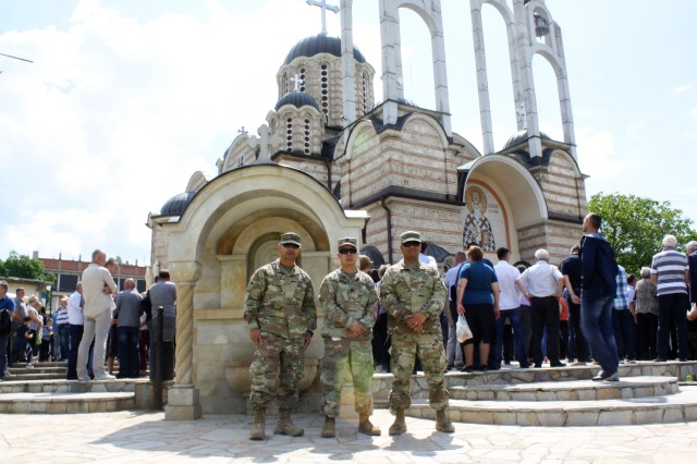 Warrant Officer 1 Mark Bun, Capt. Ronald Manlangit and Chief Warrant Officer 2 Richard Lomboy, California National Guard Soldiers serving with KFOR's Multi-National Battle Group - East, pose for a photo in front of Saint Vasilije Ostroski Church on May 19 in Leposavic, Kosovo.