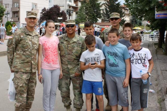 Cal Guard Soldiers Maj. James Mendoza, Maj. Fernando Perez and Maj. Amir Bahadori pose for a photo with local children during the Saint Vasilije Ostroski Festival on May 19 in Leposavic, Kosovo.