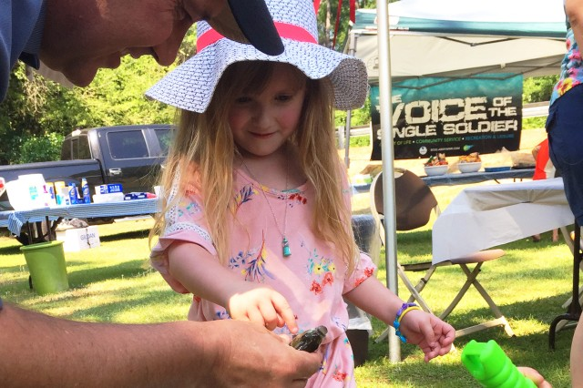 Command Sgt. Maj. Christopher D. Spivey, Fort Rucker garrison command sergeant major, examines a catch with Melania Hood, military family member, during the Hearts Apart Fishing with BOSS at Parcours Lake May 12.