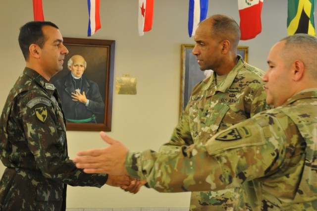 Maj. Gen. Gary M. Brito, second from right, commanding general of the Maneuver Center of Excellence, congratulates Brazilian army Lt. Col. Rafael Novaes on his selection as TRADOC Educator of the Year during a recent visit to the Western Hemisphere Institute for Security Cooperation. The institute's commandant, Col. Robert F. Alvaro, far right, is acting as Brito's guide on a tour of WHINSEC. (U.S. Army photo by Lee Rials, WHINSEC Public Affairs)