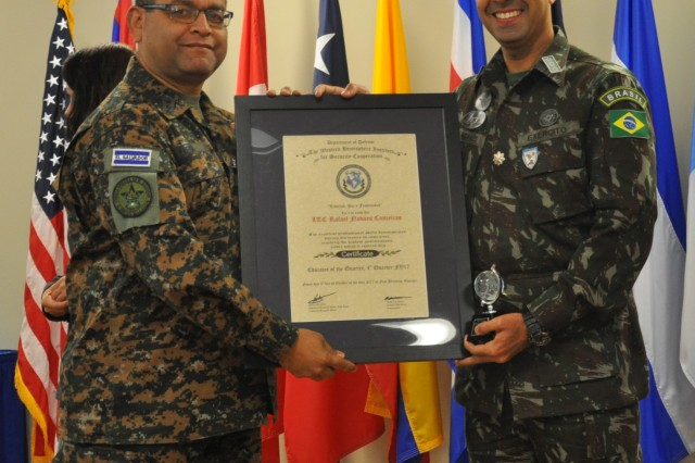 Brazilian army Lt. Col. Rafael Novaes, right, holds the trophy and document that recognized him as Educator of the Quarter during the fourth quarter of 2017. The deputy commandant of the Western Hemisphere Institute for Security Cooperation, El Salvador army Col. Luis Viera, left, presents the items. Novaes went on to win WHINSEC Educator of the Year and then TRADOC Educator of the Year. (U.S. Army photo by Lee Rials, WHINSEC Public Affairs)