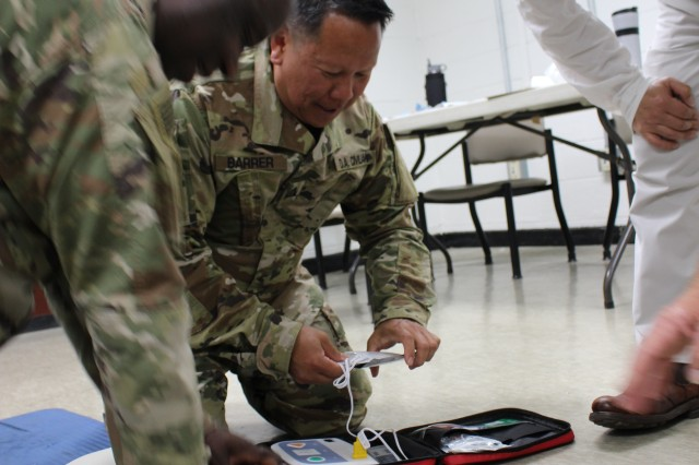 837th senior enlisted advisor, LaVaughn Brown performs CPR and deputy chief of operations, Ron Barrer readies the AED, as logistics director, Philip Yi, looks on during first aid training at the battalion on April 30.